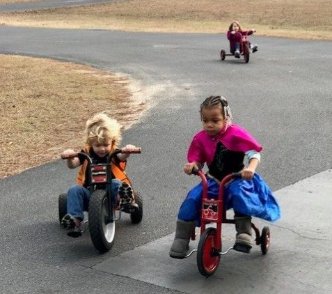 3 children playing outside on tricycles