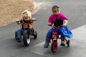 children playing outside on tricycles